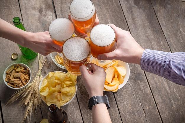 Ludzkie ręce i szklanki piwa