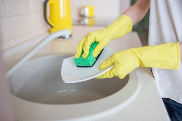 Ludzkie ręce myją naczynia. ludzie używają zielonej gąbki i noszą żółte rękawiczki.