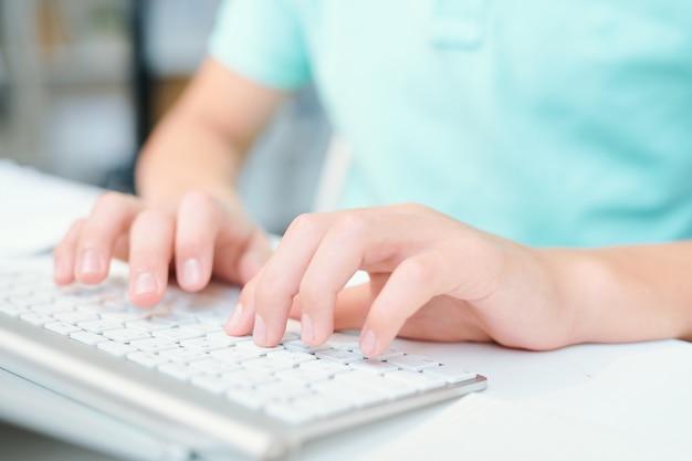 Ludzkie ręce naciskając klawisze klawiatury komputera, siedząc przy biurku w klasie lub w biurze