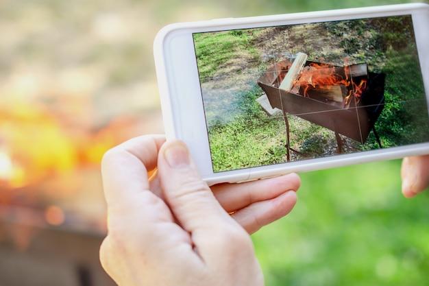 Ludzkie ręce robią zdjęcia ognia na smartfonie. na dworze.