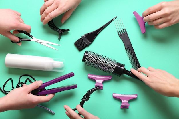 Ludzkie ręce, trzymając fryzjer na turkusowej powierzchni