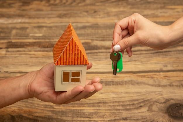 Ludzkie ręce trzymając ozdobę na białym tle na drewniane tła. koncepcja uroczystości, wakacji, rodziny, komfortu w domu. prezent na szczęśliwe czasy.