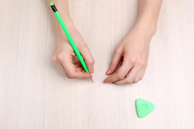 Ludzkie ręce z ołówkiem i gumką na drewnianym stole