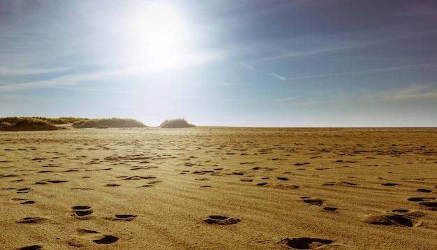 Ludzkie ślady na żółtym luźnym piasku o zachodzie słońca