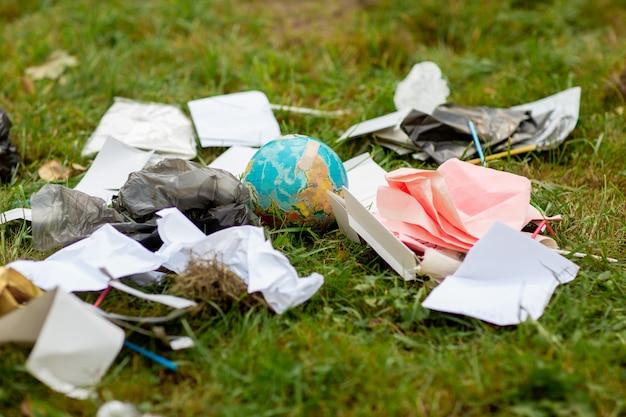 Ludzkie zaniedbanie. kula ziemska w stosie rozrzuconych śmieci na tle zielonej trawie.