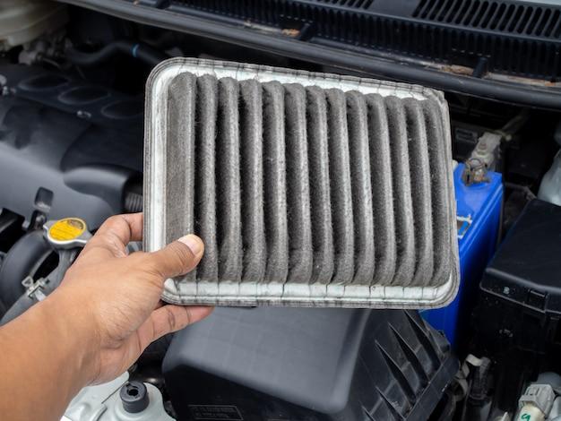 Ludzkiego ręka chwyta brudny lotniczy filtr w samochodzie, pojęcie czyścić i sprawdzać lotniczego filtr.