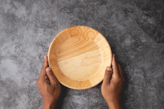 Ludzkiego ręka chwyta pusty drewniany talerz na cement ściany tekstury tle.