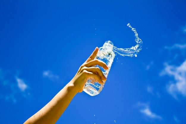 Ludzkiej dłoni trzymającej butelkę wody