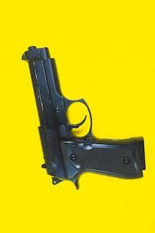 Lufa czarnego pistoletu, pistolet leży na żółtym tle. ścieśniać.