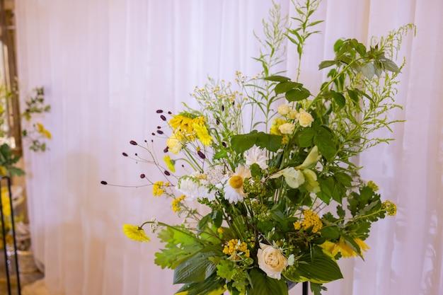 Łuk do ceremonii ślubnej ozdobiony kwiatami z tkaniny i zielenią znajduje się w sosnowym lesie