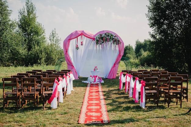 Łuk i krzesła do ceremonii ozdobione białymi i różowymi kwiatami