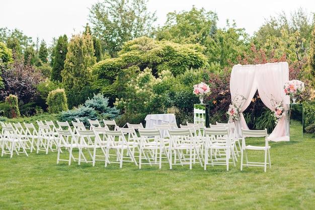 Łuk i krzesła do ceremonii ślubnej, ozdobione tkaniną i kompozycjami kwiatowymi