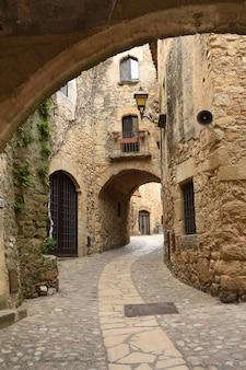 Łuk i ulica starego miasta średniowiecznej wioski pals, prowincja girona, katalonia, hiszpania