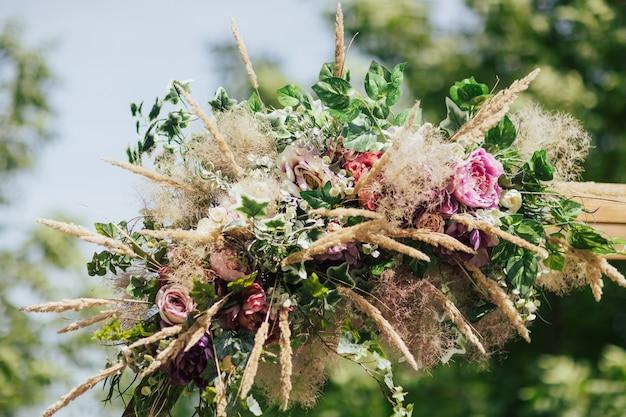 Łuk na ceremonię ślubną ozdobiony kwiatami i zielenią