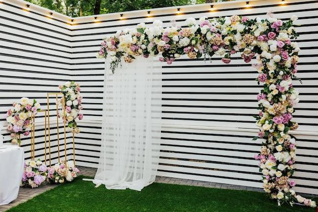 Łuk na ceremonię ślubną, tkanina dekoracyjna, kwiaty i zieleń.