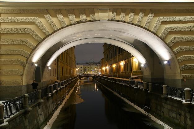 Łuk nad rzeką z odblaskowymi latarniami i budynkami w zimowy wieczór