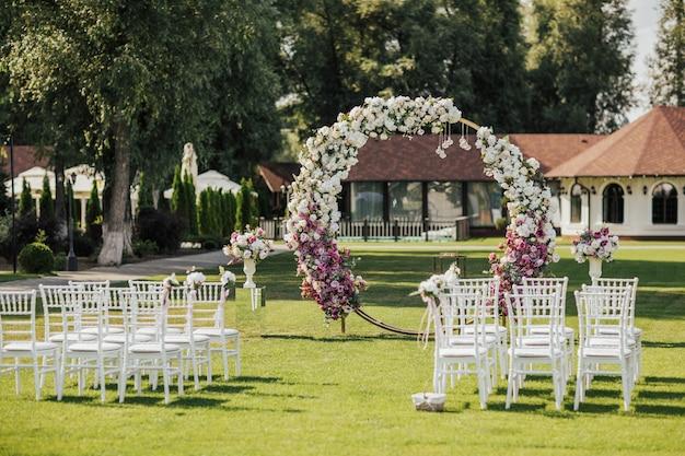 Łuk, ozdobiony różowo-białymi kwiatami stojącymi w parku