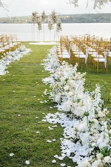 Łuk premium do ceremonii ślubnej dla nowożeńców nad brzegiem rzeki z glicyniami. puste krzesła i parasole
