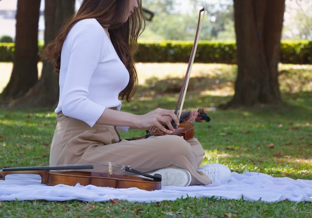 Łuk skrzypiec trzymany przez damę za rękę, przygotowujący się do gry, w parku, rozmyte światło dookoła