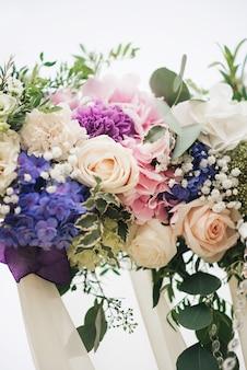 Łuk ślubny ozdobiony tkaniną i kwiatami na zewnątrz. piękny ślub. ślubna ceremonia na zielonym gazonie w ogródzie.