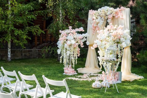 Łuk ślubny ozdobiony tkaniną i kwiatami na zewnątrz.