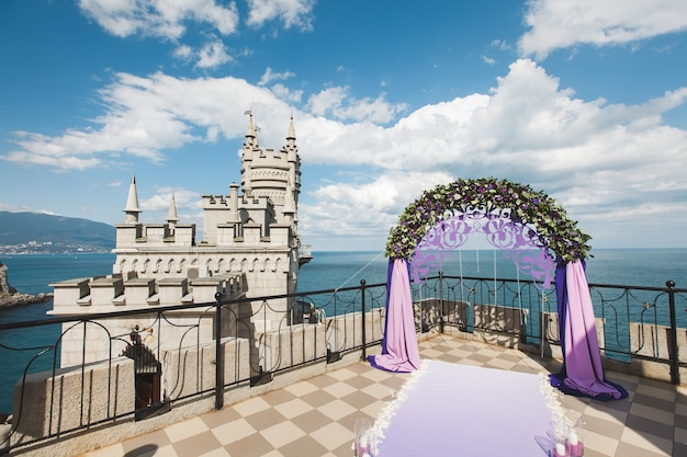 Łuk ślubny w kolorze fioletowym na tle morza.