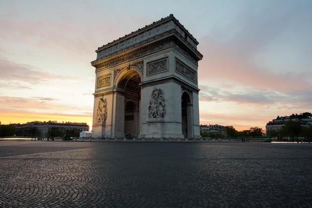 Łuk triumfalny i pola elizejskie, zabytki w centrum paryża, o zachodzie słońca. paryż, francja