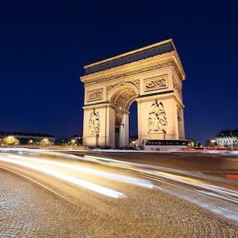 Łuk triumfalny nocą ze światłami samochodowymi, paryż, francja
