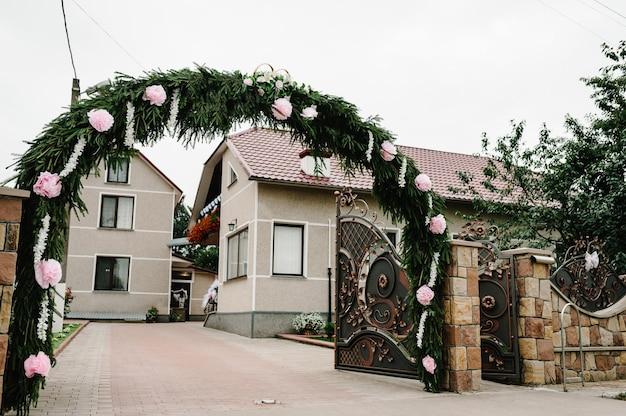 Łuk zdobiony kwiatami i brama wjazdowa, dziedziniec z domem. poranne przygotowania do ślubu.