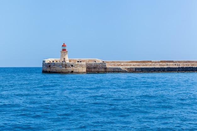 Łukowa kładka dla pieszych z latarnią morską św. elma położona w pobliżu brzegu miasta valletta