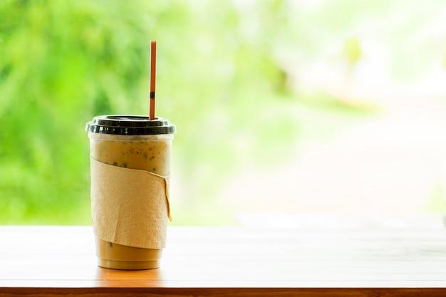Lukrowa kawa w takeaway filiżance i zamazanym tło abstrakcie.
