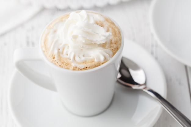 Lukrowa kawa z batożącym mlekiem i karmelu lody w wysokich szkłach na nieociosanym drewnianym stole, selekcyjna ostrość