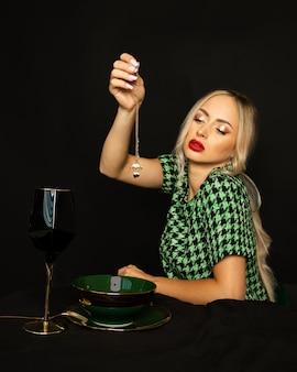 Luksusowa blondynka, portret na czarnym tle, strzał studio, koncepcja luksusowy styl życia, zjada złotą biżuterię. zdjęcie