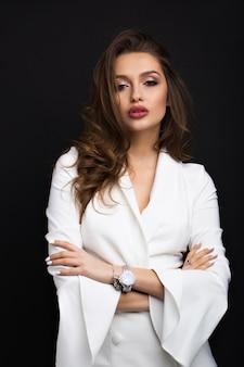 Luksusowa brunetka w białej sukni na czarnym tle