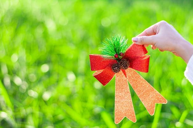 Luksusowa czerwona wstążka w ręce młodych kobiet. - koncepcja prezentu bożonarodzeniowego.