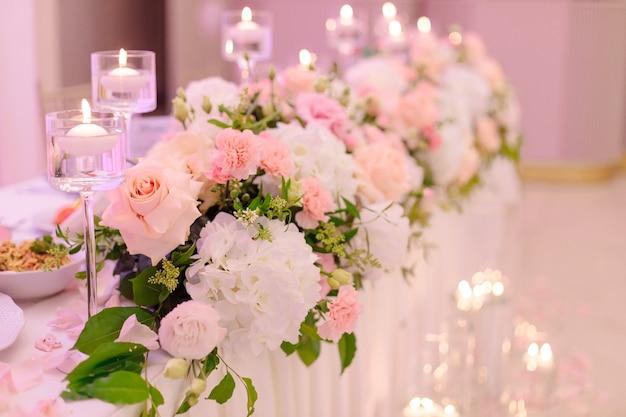 Luksusowa dekoracja stołu weselnego z girlandami kwiatów i płonącymi świecami. florystyka ślubna. koncepcja imprez weselnych. piękno i luksus. styl życia.