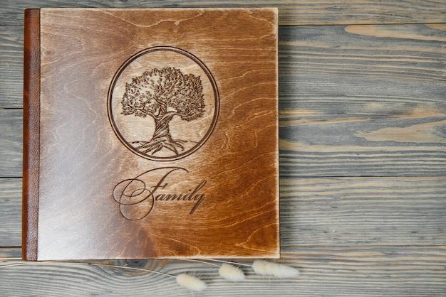 Luksusowa drewniana fotoksiążka na naturalnym tle. fotoksiążka ze wspomnieniami rodzinnymi. zachowaj wspomnienia z letnich wakacji.