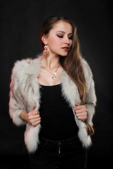 Luksusowa dziewczyna z długimi brązowymi włosami w futrze. królowa śniegu. zimna dziewczyna. ryś, futro, moda, uroda. wiatr, ciemne tło. salon futrzany, północ
