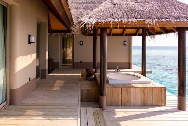 Luksusowa fasada bardzo drogiej, bogatej willi na wodzie na malediwach, ozdobiona naturalnym drewnem.