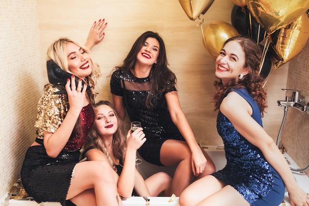 Luksusowa impreza w stylu mody. eleganckie dziewczyny wygłupiające się w łazience z balonami. pijana pani rozmawia na jej bucie.