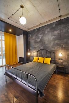 Luksusowa kawalerka o swobodnym rozkładzie w stylu loftowym w ciemnej i żółtej kolorystyce