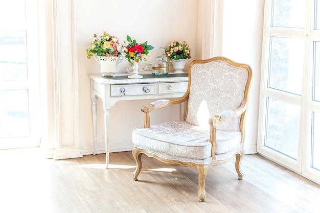 Luksusowa, klasyczna biała sypialnia w stylu barokowym z dużym oknem i fotelem