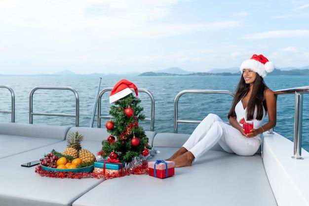 Luksusowa kobieta w białym garniturze i czapce mikołaja świętuje nowy rok na tropikalnym rejsie jachtem.
