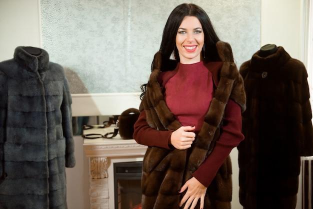 Luksusowa koncepcja odzieży. kobieta z futrem. dziewczyna w płaszcz futra w sklepie z futra na tle.