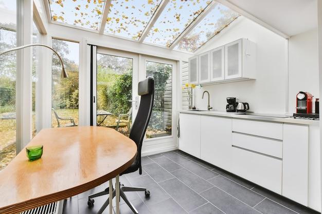 Luksusowa kuchnia domowa z białymi szafkami i stołem do pracy przy szklanej ścianie w budynku mansardowym ze szklanymi oknami w sufitach