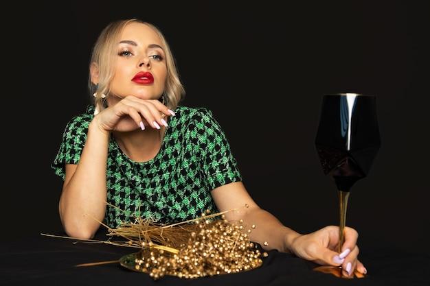 Luksusowa młoda blondynki kobieta w zielonej sukni na czarnym tle nudzi się na diecie. koncepcja zaburzeń odżywiania. zdjęcia studyjne