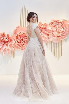 Luksusowa panna młoda w pięknej drogiej sukni ślubnej na tle dużych sztucznych kwiatów. dziewczyna w białej wakacyjnej sukience, idealne włosy i makijaż. koronkowa sukienka na ciało młodej kobiety