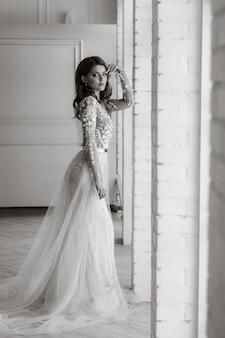 Luksusowa panna młoda w sukni ślubnej rano w jej wnętrzu. czarno-białe zdjęcie.