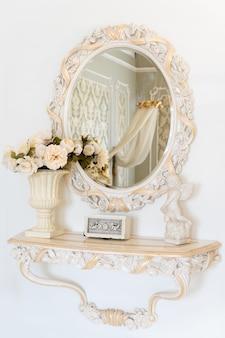 Luksusowa ściana sypialni w jasnych kolorach z lustrem. eleganckie klasyczne wnętrze