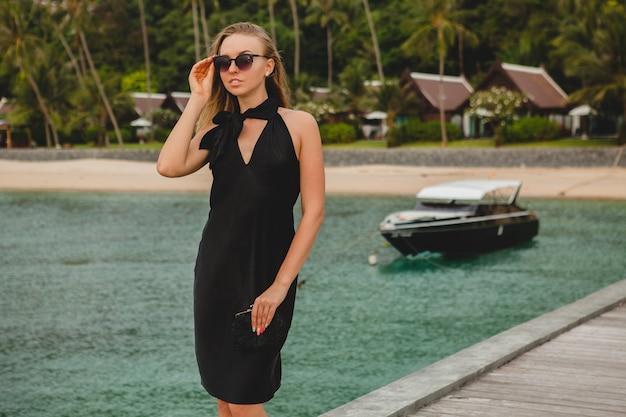 Luksusowa seksowna atrakcyjna kobieta ubrana w czarną sukienkę, pozowanie na molo w luksusowym hotelu, na sobie okulary przeciwsłoneczne, wakacje, tropikalna plaża